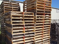 Stacks of recycled 4 way stringer pallets
